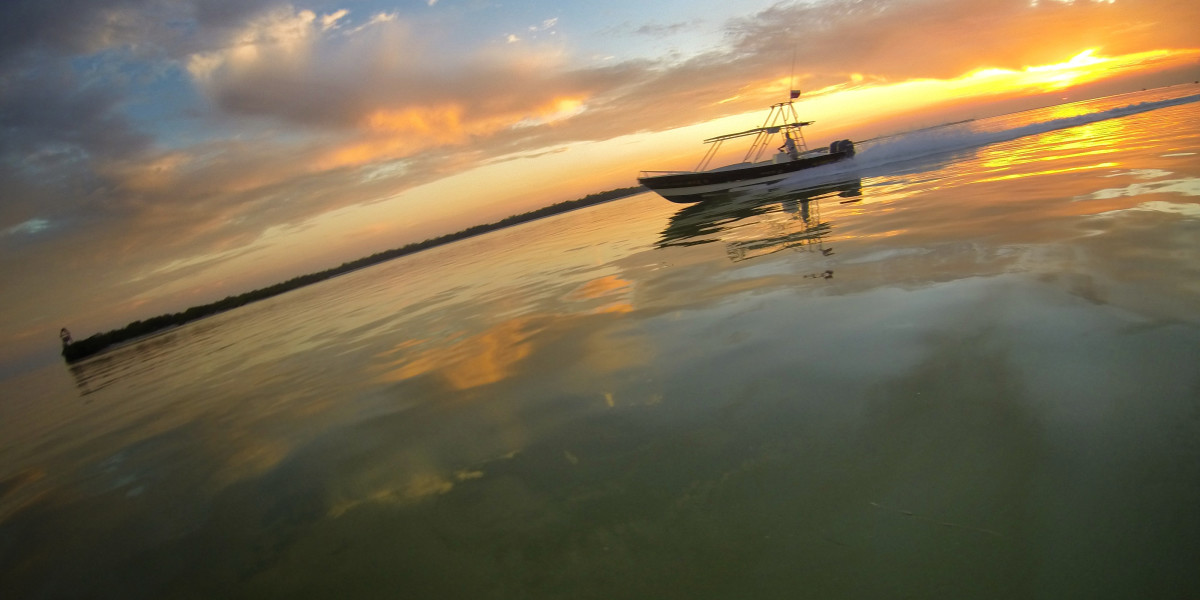 Tour boat passes by Isla Passion in Holbox with the sunrise in the back