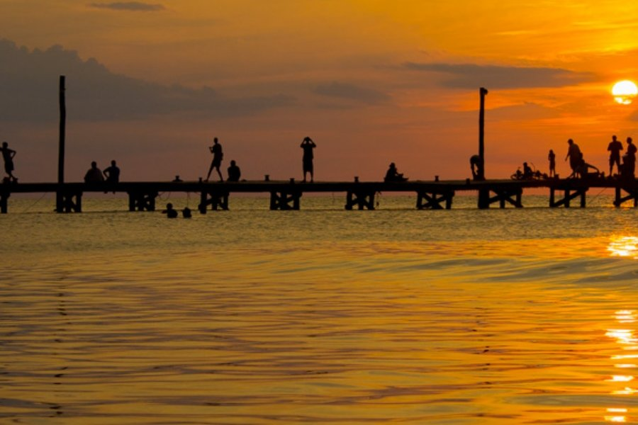 Holbox Sunset silhouettes tourists and locals on the pier with a rich orange glow