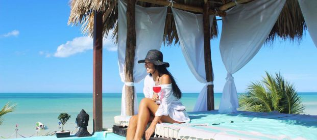 A young woman lounging on a bedside pool with her feet in the water at Alma Bar with a view of the Holbox sea behind