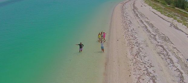 A birds eye view of a group of people on the shore of Holbox looking up