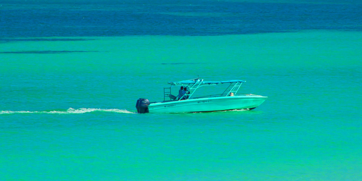 A turquoise tour boat blends in with the colourful Holbox sea