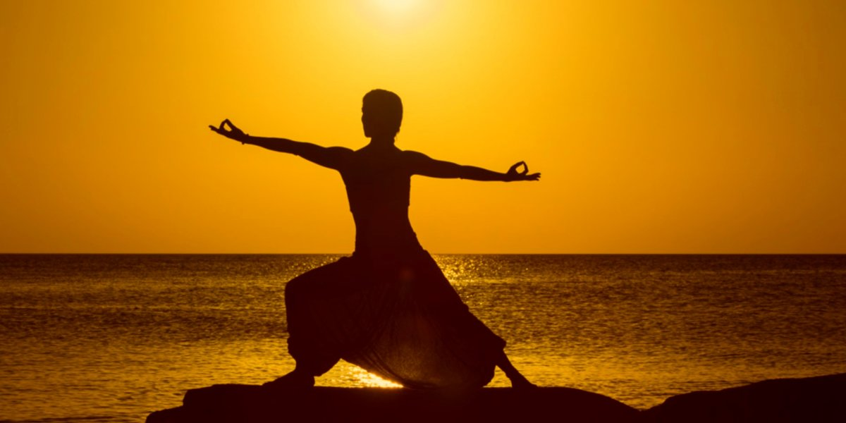 The silhouette of  a female yogi posing by the beach with the yellow sky and sun in the back