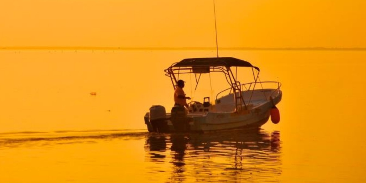 A fisherman in his fishingboat at dawn in Holbox's Laguna Conil