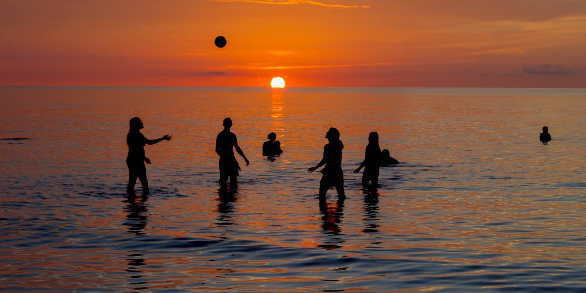 Holbox Island visitors playing with a ball in the sea with the sunset behind them