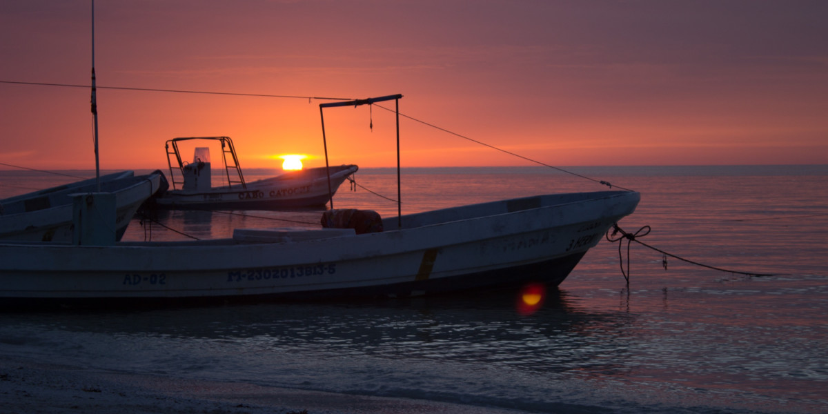 Two small fishing boats anchored on the beach of Holbox with a purple sunset
