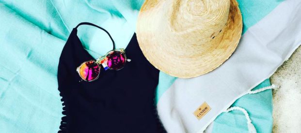 Beach apparel and accessories: a straw hat, sunglasses and a beach throw from Le Bazaar Boutique