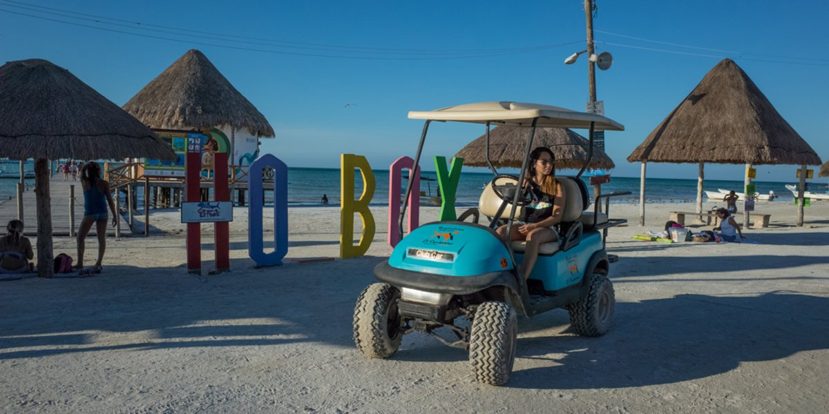 A young woman driving a rental golf cart next to the Isla Holbox wooden pier on a sunny day.