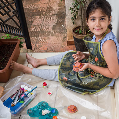Little girl painting a clay diya