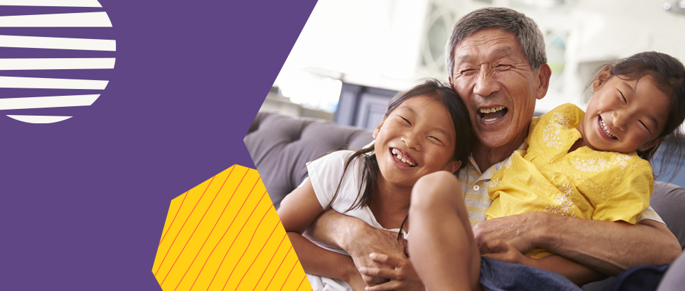 An elderly asian man hugging his grandchildren all laughing