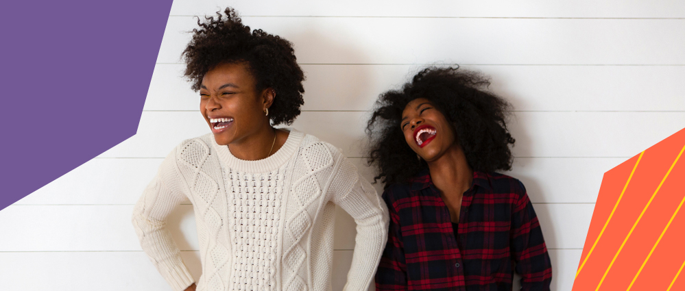 two black women with beautiful afro hair smiling