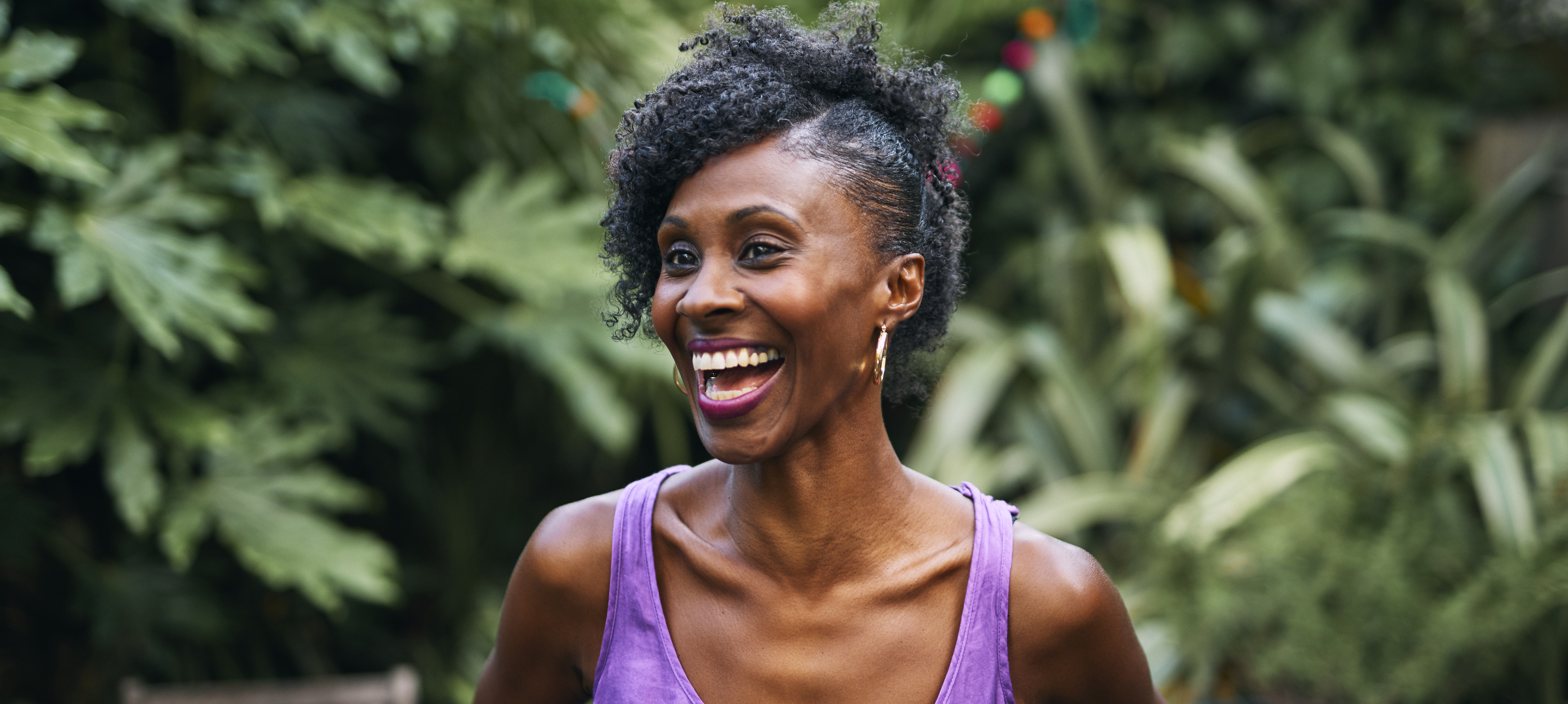 Happy woman standing in front of trees in a purple top laughing at the camera