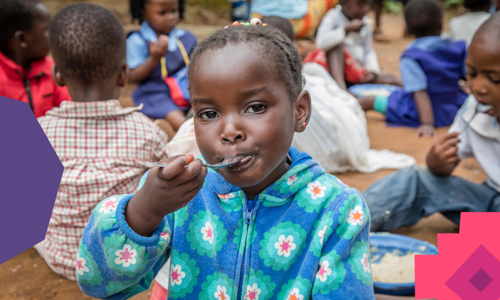 A young black girl in a camp eating food with a spoon