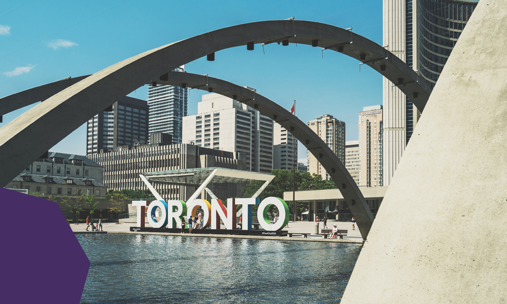 """A toronto sign near a water with high rise buildings at the background """"A"""