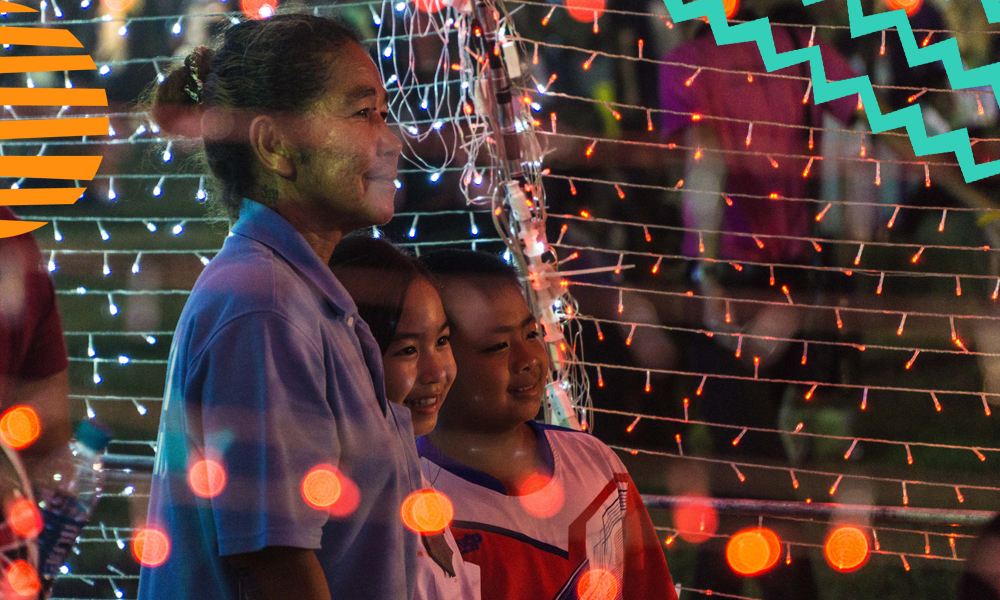 "a mother with her two children standing in front of a fence with christmas bulbs""A"