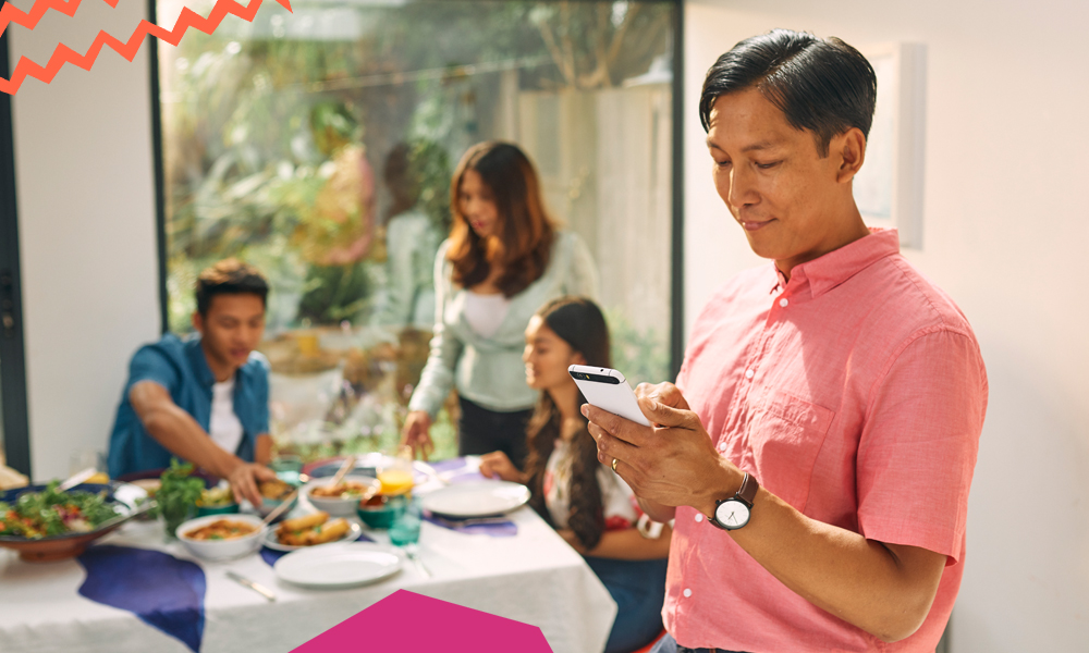 """a man sending money to philippines holding his phone and his family is dining at the background""""A"""