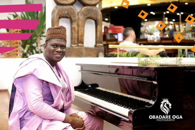 "stephen akintayo in a native clothing besides a piano""A"