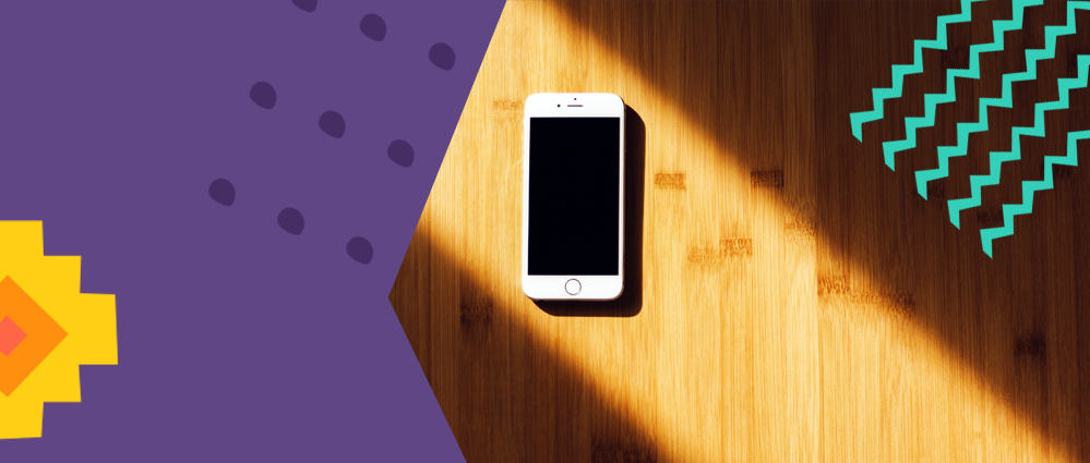 A phone laying on a wooden table with a sunlight string