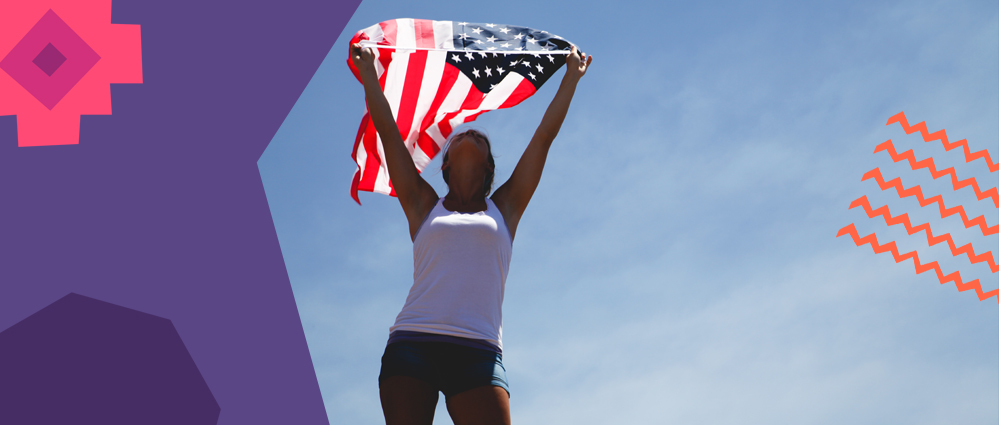 a woman holding a US flag above her head