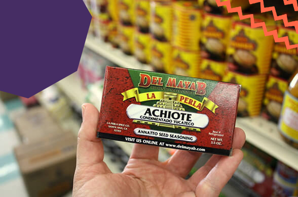 "a hand holding achiote paste in a shop""A"