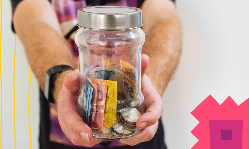 "a man holding a jar with money""A"