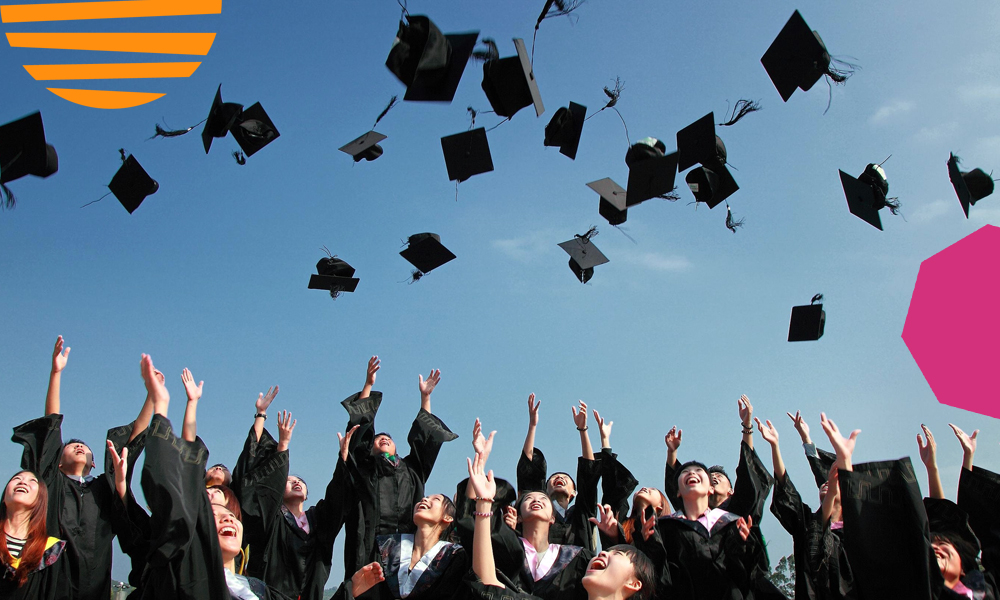"egroup of students during graduation throwing their hats up in the air""A"