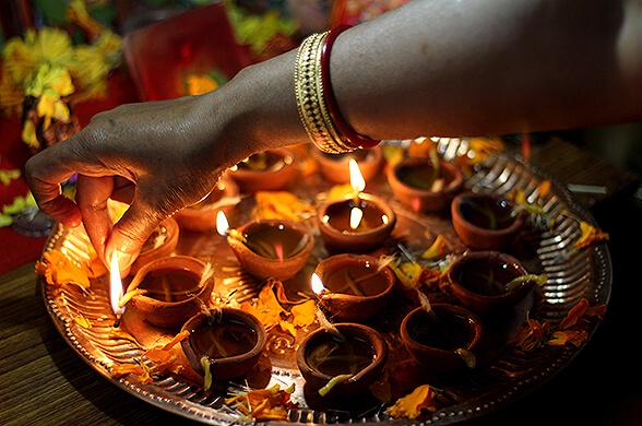 Clay diyas - oil lamps - being lit to celebrate Diwali