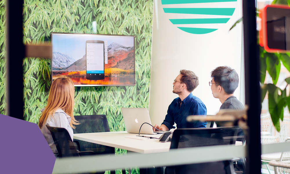 "blond woman and two men sitting in a meeting room looking at a tv screen""A"