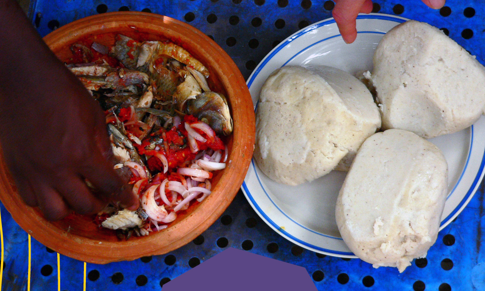 "banku dumplings on a blue table with black and white hands reaching to it ""A"