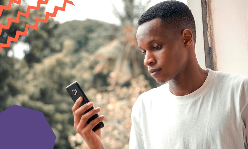 "an african boy in a white tshirt holding a black phone""A"