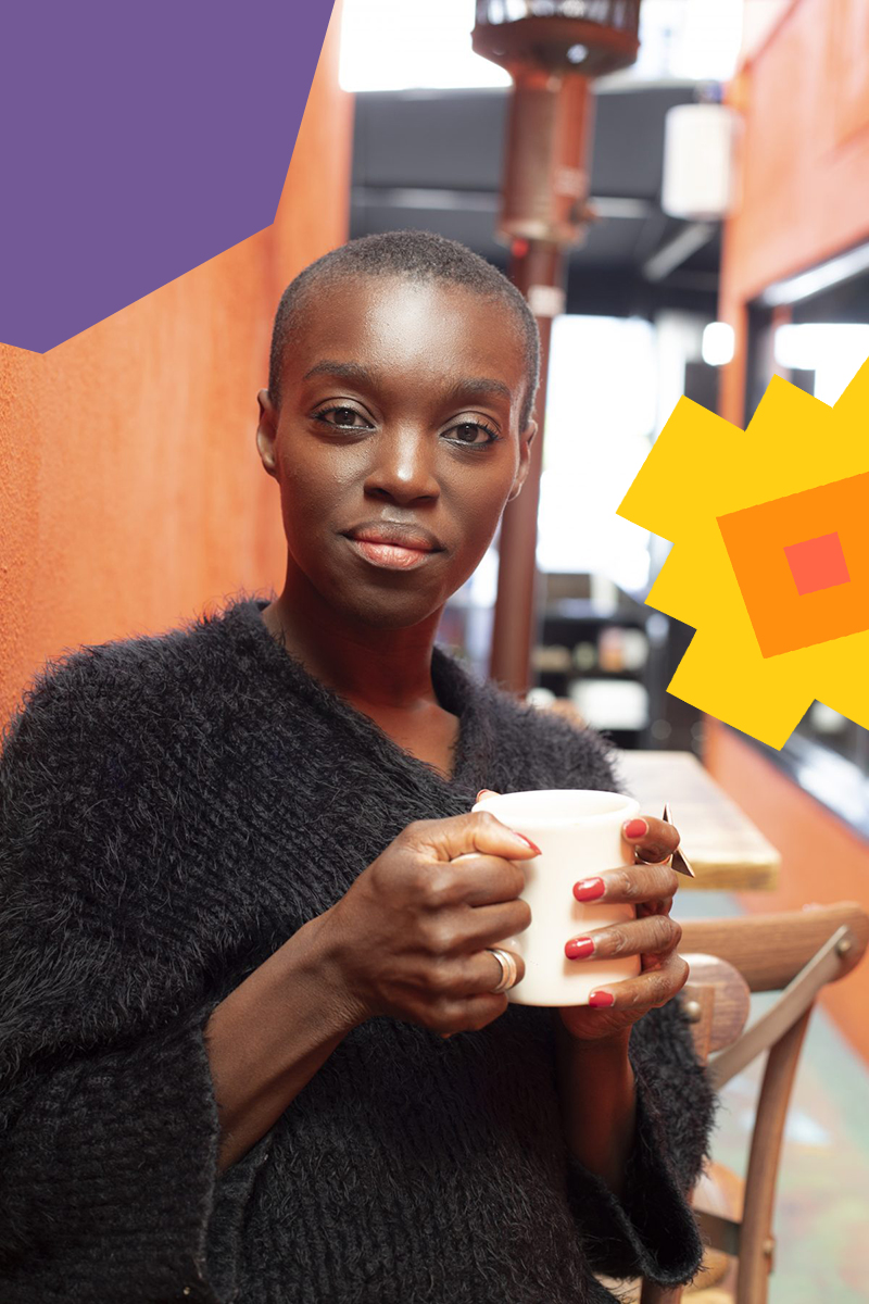 "Former dancer and now a wellness coach Isa Welly Locoh-Donou wearing a black jumper holding a white mug""A"