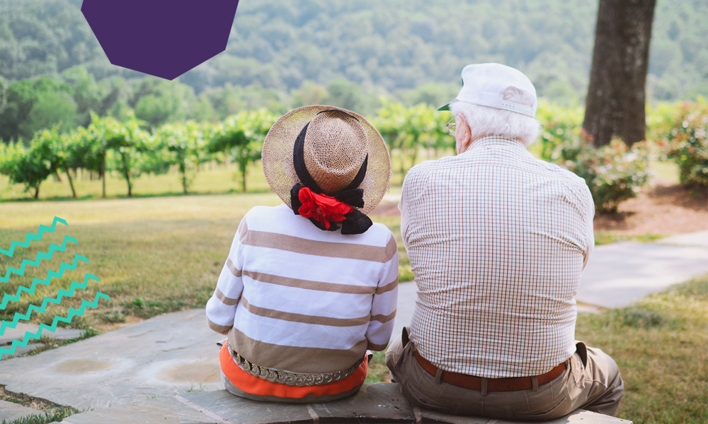 "Older couple sitting on a big stone looking at mountains together""A"