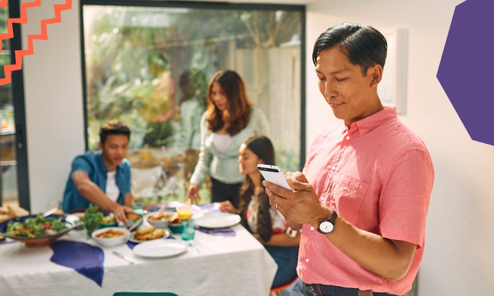 "a man holding his phone besides a table with his family sending a fast online money transfer""A"