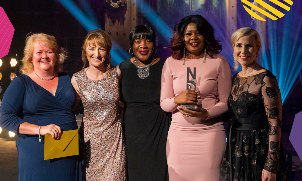 """Codilia Gapare holding a national diversity award surrounded by females""""A"""