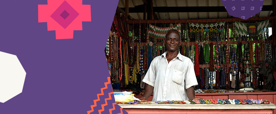 Ghanaian beads merchant Garbe Mohammed in a white shirt and a smile on his face standing in his stool surrounded by colourful ghanaian beads