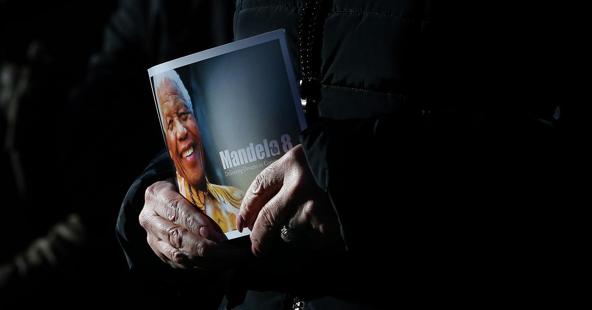 A close up at hands holding a leaflet of Mandela8 organisation