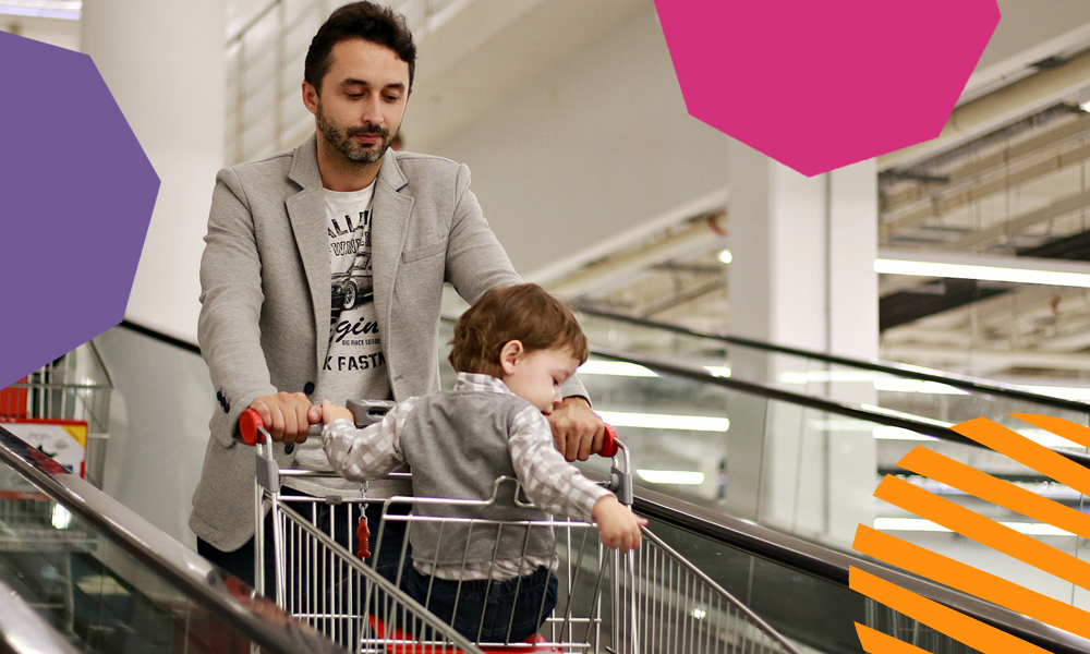 """an adult man with a child in a trolley on an escalator""""A"""