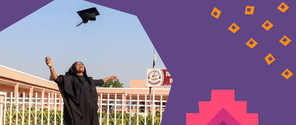 Young female african student graduating wearing a black robe throwing her hat above her