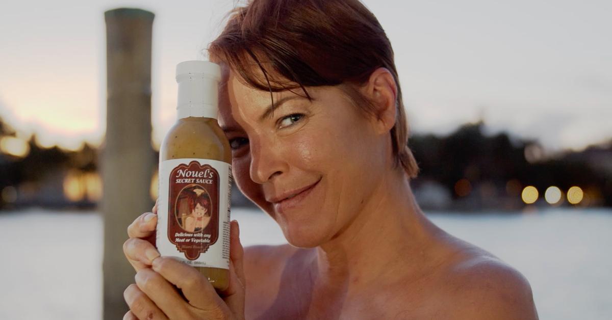 Nouele Estrela smiling at a camera and holding her secret sauce bottle