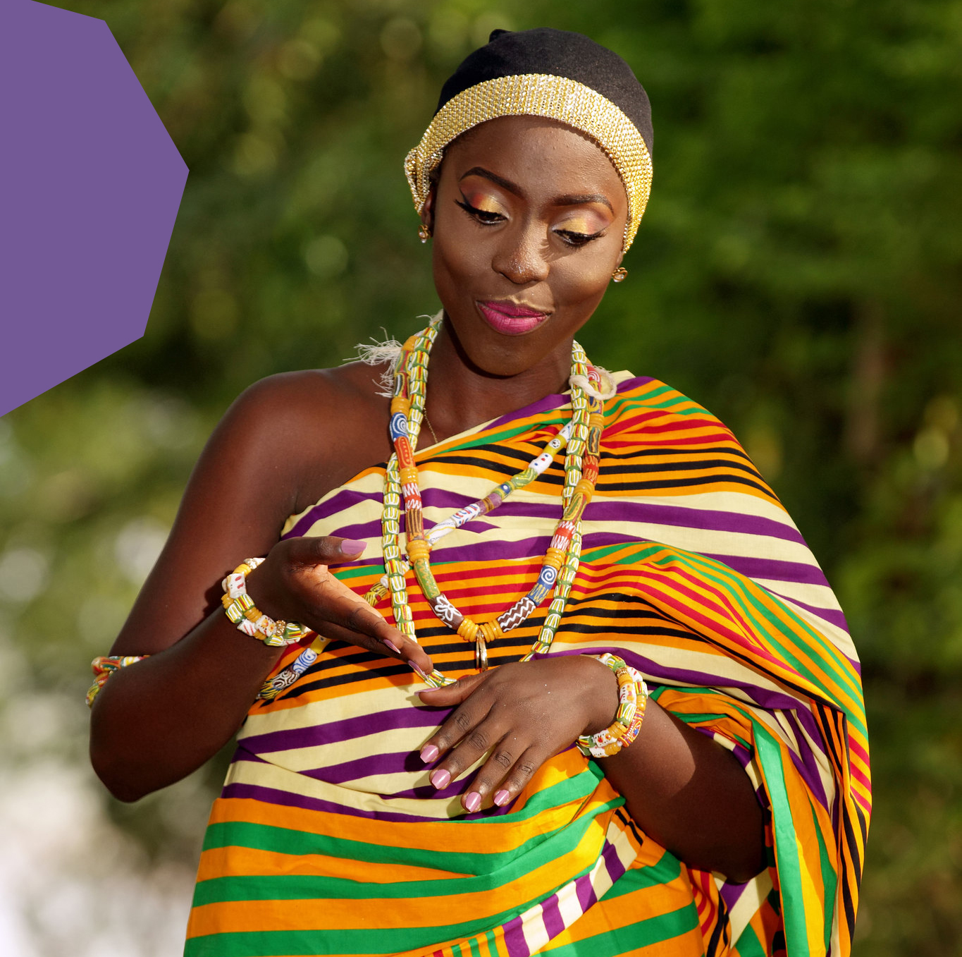 A Ghanaian woman in a kente cloth of stripes looking down