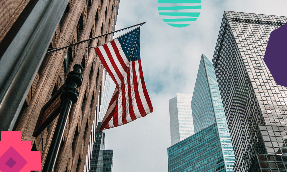 """A US flag handing on a bulding on a street with high-rise buildings in the background""""A"""