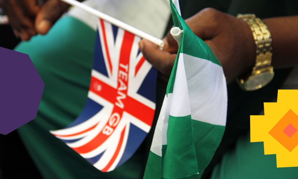 "a nigerian man holding a nigerian and british flag""A"