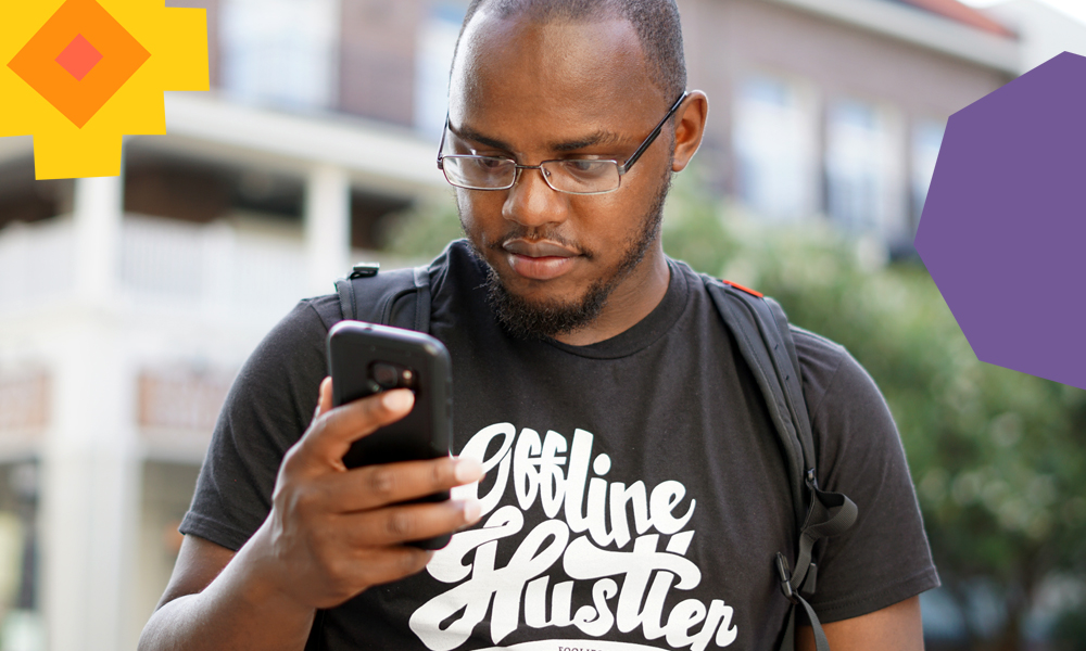 "a man sending money on his phone wearing a black tshirt standing on the street        ""A"