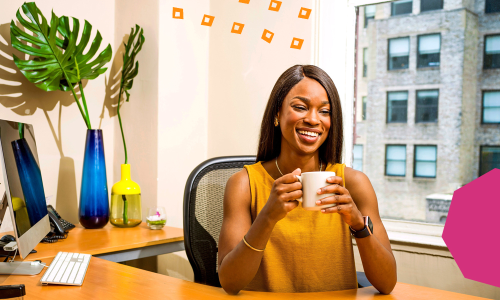 "A smiling woman dressed in orange top sitting in the office and holding a cup      ""A"
