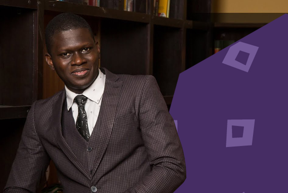 """stephen akintoyo in a brown suit standing against a purple background""""A"""