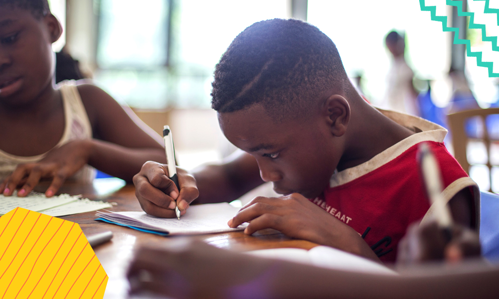"""a young boy in africa holding a pen and writing something in his textbook in school picture by worldremit celebrating edtech in africa """"A"""
