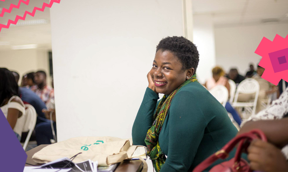 "Heather Mavunga with short hair dressed in a green jumper sitting in a conference room smiling""A"