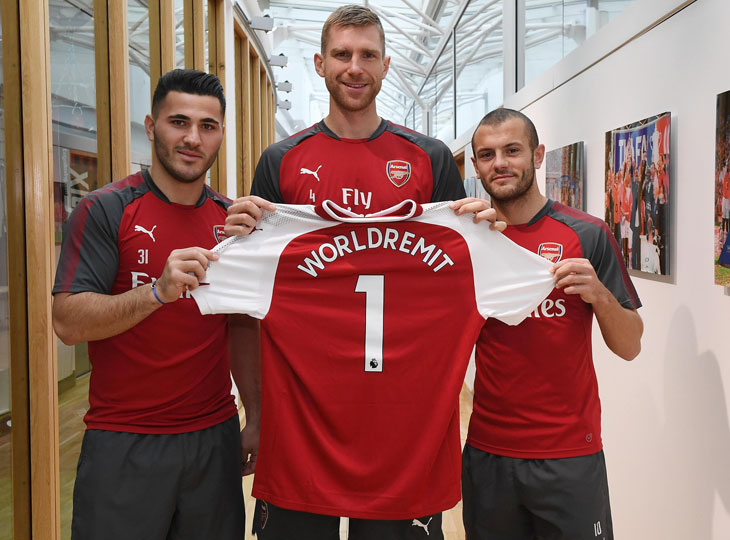Sead Kolasinac, Per Mertesacker and Jack Wilshire smile for the camera as they hold a red Arsenal jersey with WorldRemit on the back.