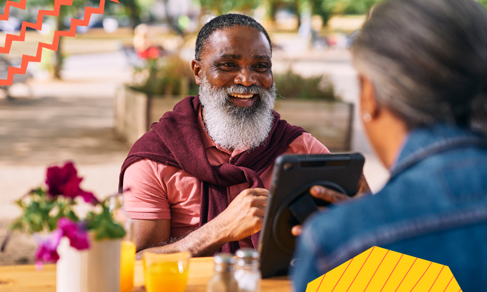 "a smiling man with a grey beard sitting by a table in front of his wife holding a tablet""A"