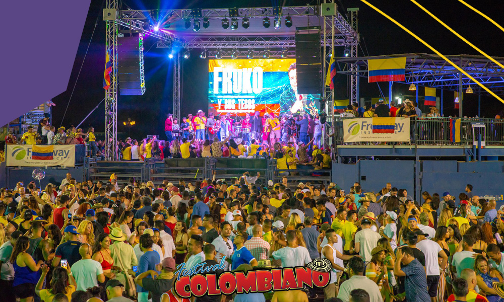 "A stage with a crowd of people dancing and celebrating during Festival Colombiano""A"