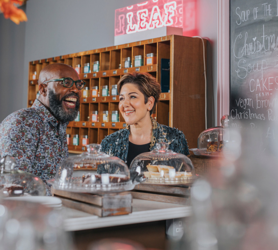 A man and a woman smiling in a cafe